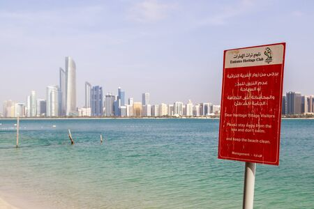 ABU DHABI, UAE, JANUARY 10, 2019: Red warning board prohibiting swimming in sea