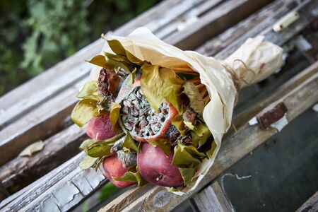 Bunch of rotten fruit and wilted flowers