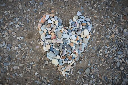 A large heart made of small pebbles Фото со стока