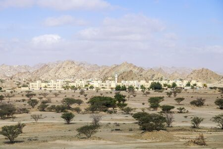 Small modern city in the United Arab Emirates in the desert at the foot of the mountains. Imagens