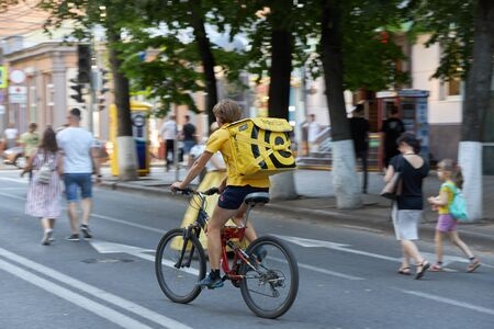 KRASNODAR, RUSSIA, AUGUST 10, 2019: Young guy, food delivery boy, rides a bicycle on the road in center of the city.