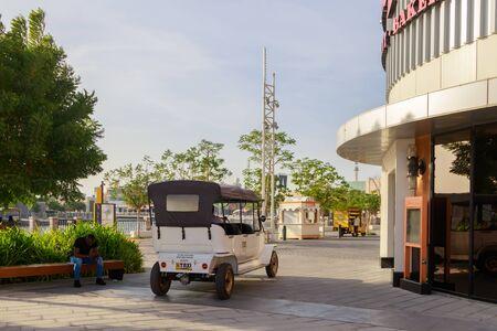 DUBAI, UAE, JANUARY 09, 2019: White electric taxi stands and waits for tourists on the area of Dubai Parks.