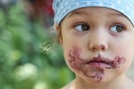 Portrait of a cute girl with a grimy mouth after eating mulberry berries Stockfoto