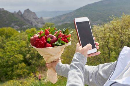 Girl takes a bouquet of red flowers and fruits on a phone camera Banque d'images - 132557265