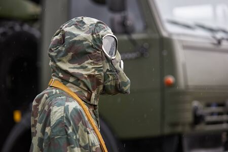 Mannequin dressed in a special camouflage chemical protection suit and gas mask stands on the background of a military truck Banque d'images - 133844651
