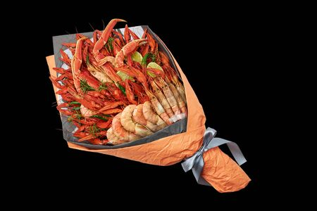 Snack for a youth party in the form of a bouquet with boiled crayfish, crabs and shrimps on a black background. Stock Photo