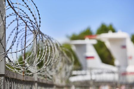 Transport aircraft stand at the airport fenced with barbed wire. Selective focus on the barbed wire fence.