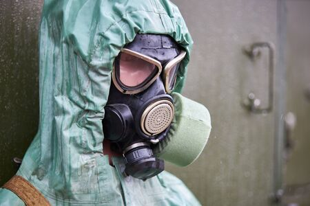Mannequin dressed in green rubber chemical protection suit and black gas mask, close-up. Banque d'images - 133844792