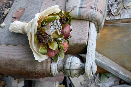 Bunch of rotten fruit and wilted flowers as a symbol of a destroyed old life.