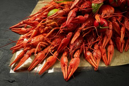 Fresh red boiled crawfish lie on a black background.