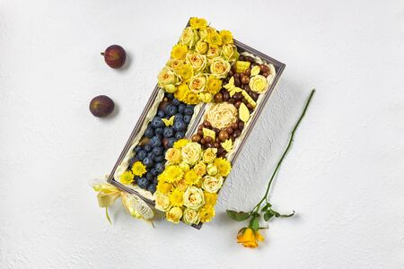 Wooden box filled with yellow flowers, blueberries and chocolate on a white background.