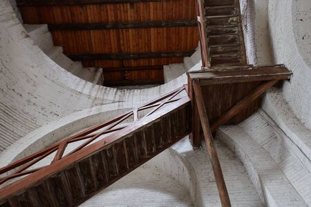 Old decrepit wooden staircase leading up inside of the building.