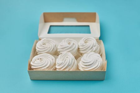 Delicious, natural handmade zephyrs stacked in a box on a turquoise background.
