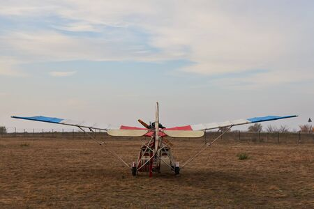 Ultralight aircraft stands on the airfield before takeoff, back view.