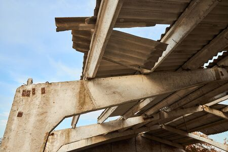 Reinforced concrete beams and a dilapidated roof of an unfinished farm for livestock.