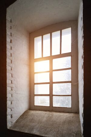Rays of the sun at sunset make their way through a large old window in a tower with thick stone walls.
