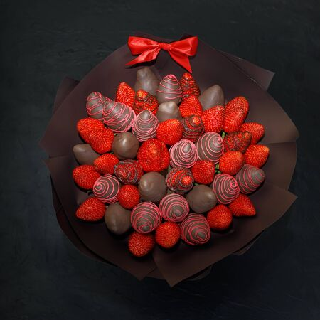 Gift bouquet collected from ripe strawberries covered with brown chocolate on a black background. View from above.