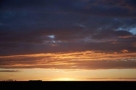 Orange rays of the sun at sunset illuminate dense clouds.