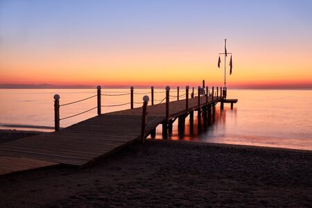 Calm warm sea and a large wooden pier with a swimming area at dawn. Stockfoto