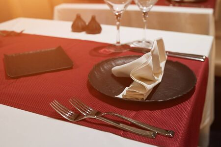 Small table in restaurant with black plates. Stockfoto
