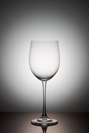 One empty transparent wine glass stands on a dark glass. Stockfoto