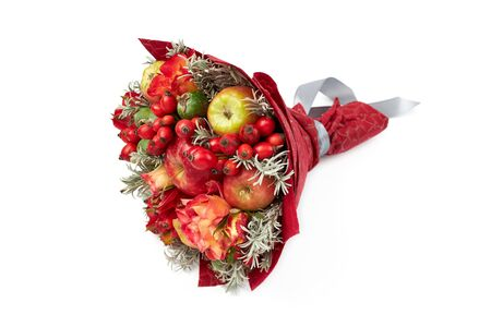 Beautiful red bright bouquet of apples, rose hips, feijoa and roses on a white background. Stockfoto