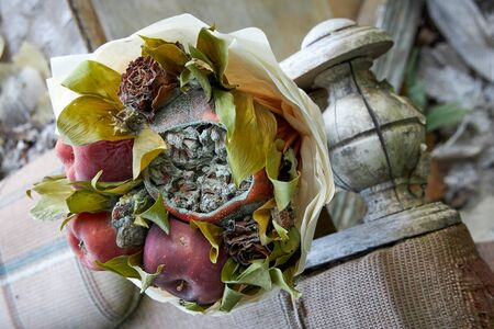 Bouquet of rotten fruit and wilted flowers as a symbol of imminent old age.
