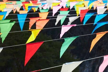 Many multi colored triangular flags hanging on the ropes as a holiday decoration.