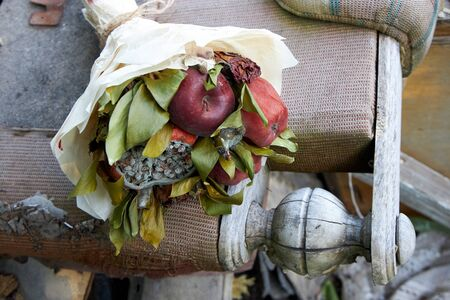 Bunch of rotten fruit and wilted flowers lie on the remains of old furniture Stock fotó