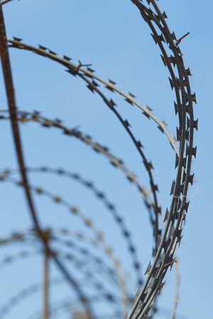 Spiral barbed wire against the blue sky, vertical image.