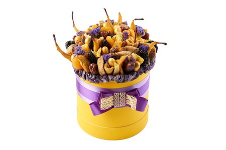 Yellow cylindrical box filled with dried fruits on a white background. Archivio Fotografico - 147855609