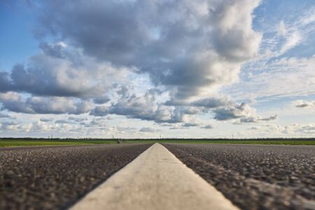 Empty asphalt road on a background of beautiful cloudy sky, close-up.