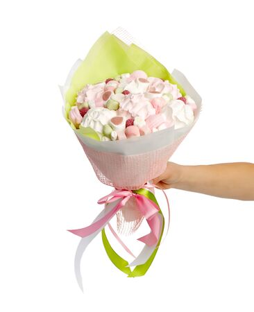 Stylish bouquet of marshmallows in a female hand on a white background.