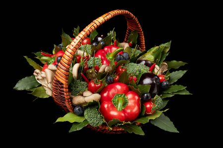 Wicker basket filled with various fresh ripe vegetables on a black background. Archivio Fotografico - 147464242