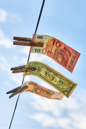 Banknotes hanging on a clothesline, as a symbol of successful investment, concept.