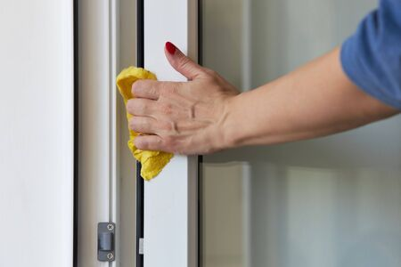 Woman washes an open door to the balcony with a yellow rag.