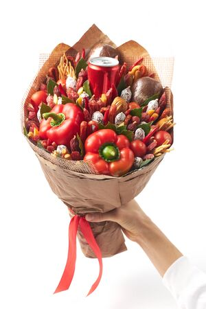 A large bouquet created from smoked sausages, cheese, paprika and bread wrapped in craft paper in a womans hand on a white background Archivio Fotografico - 147855627