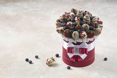 Round box filled with chocolate covered strawberries and ripe blueberries on a marble background as a template for a birthday invitation card.