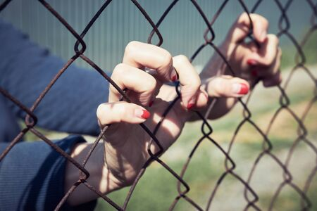 Female hands grabbed the metal mesh of the fence, concept. Archivio Fotografico - 147855633