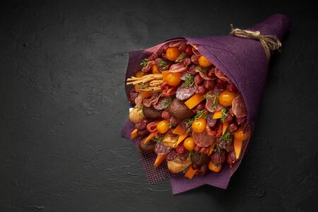 Unique bouquet for a man consisting of sausages, cheese, tomatoes and dark bread on the black background.