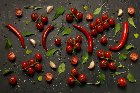 A lot of cherry tomatoes, hot pepper pods, leaves of rucola and salad, garlic and spices lie on a black background. Archivio Fotografico - 147856281
