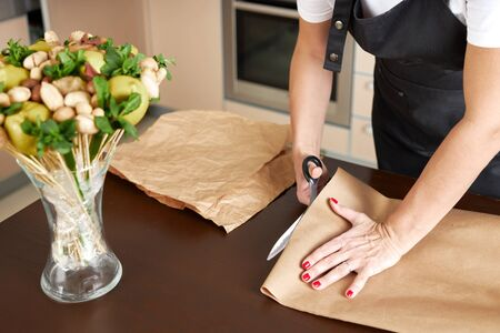 Female decorator cuts craft paper for packing a fruit bouquet. Archivio Fotografico