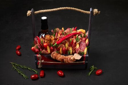 Wooden box filled with smoked sausages, cheese, tomatoes and a bottle of whiskey on a black background. Archivio Fotografico - 147466838
