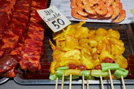 Barbecue sticks with crocodile meat lies on a counter in a market in Thailand. Archivio Fotografico - 147465746