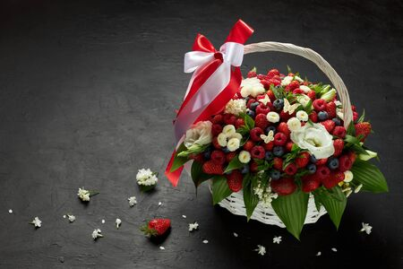 Large basket filled with strawberries, raspberries, blueberries decorated with white flowers on a black background.