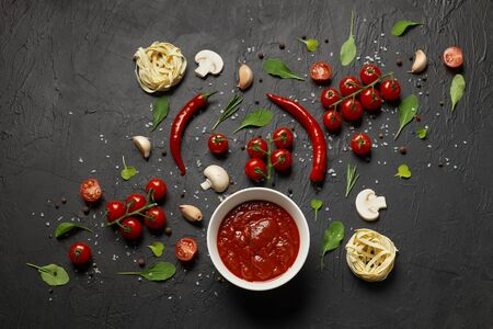 Tomato sauce and ingredients for its preparation, such as cherry tomatoes, red pepper, garlic, mushrooms and spices on a black background Archivio Fotografico