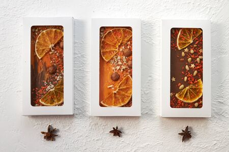 Three handmade chocolate bars with nuts and dried fruits on a white background. Archivio Fotografico - 147856289