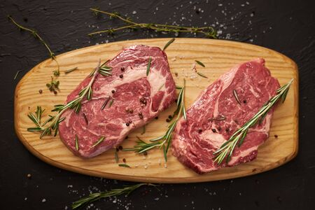 Two raw beef steaks lie on a wooden board, Top View.