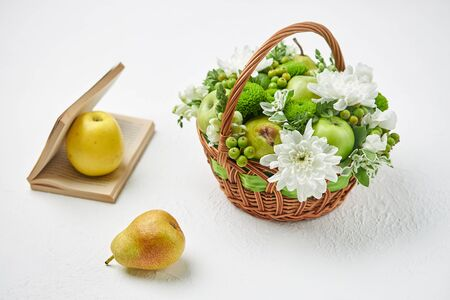 Still life with a wicker basket filled with fruits, white flowers and an open book. Archivio Fotografico - 147467046