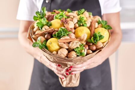 A large beautiful fruit bouquet of lemons, nuts, ginger and mint in the hands of a woman florist. Archivio Fotografico - 147856291